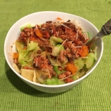 Pappardelle and zucchini noodles topped with meat sauce and parmesan cheese