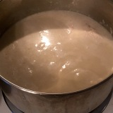 Coconut milk and broth about to boil, with chicken breasts just below the surface.