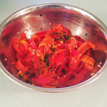 Roasted red peppers, sliced into strips and combined with parsley and garlic.