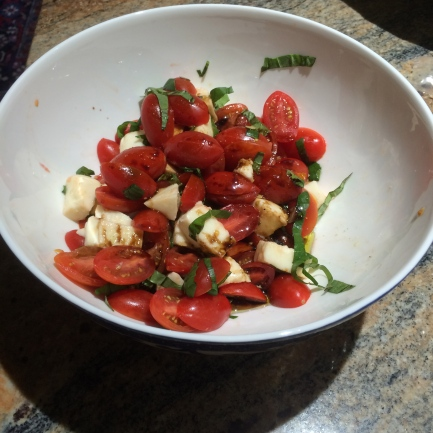 Caprese salad with cherry tomatoes, mozarella, basil, balsamic and olive oil.