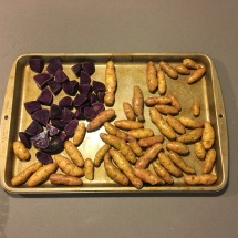 A sheet pan with purple potatoes and fingerling potatoes.