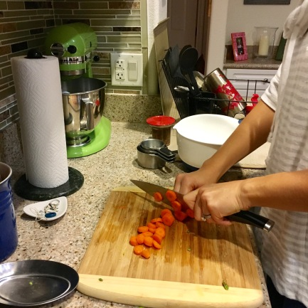 Left-handed Liz cuts carrots for roasting.