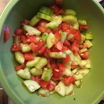 Cucumbers and tomatoes sit in salt and pepper while the rest of the ingredients are assembled.