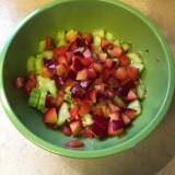 Cucumber, tomatoes and plums, ready for dressing.