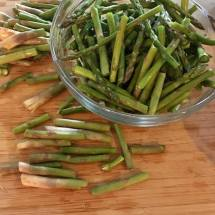 Snap the dried ends off from stemmed asparagus, and just keep snapping stems into smaller pieces for cooking.