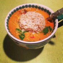 Crab soup, topped with a rounded scoop of brown rice.