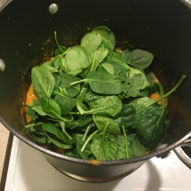 Handfuls of fresh spinach wilt quickly under the pot's lid.