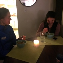Loretta and Taylor sampling soup by candlelight.
